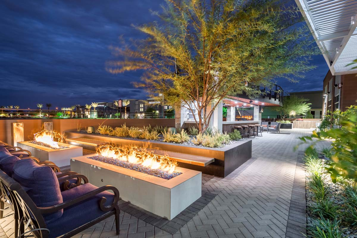 Custom landscape and hardscape commercial patio area with brick pavers, large bar area, expansive fire pits and seating area