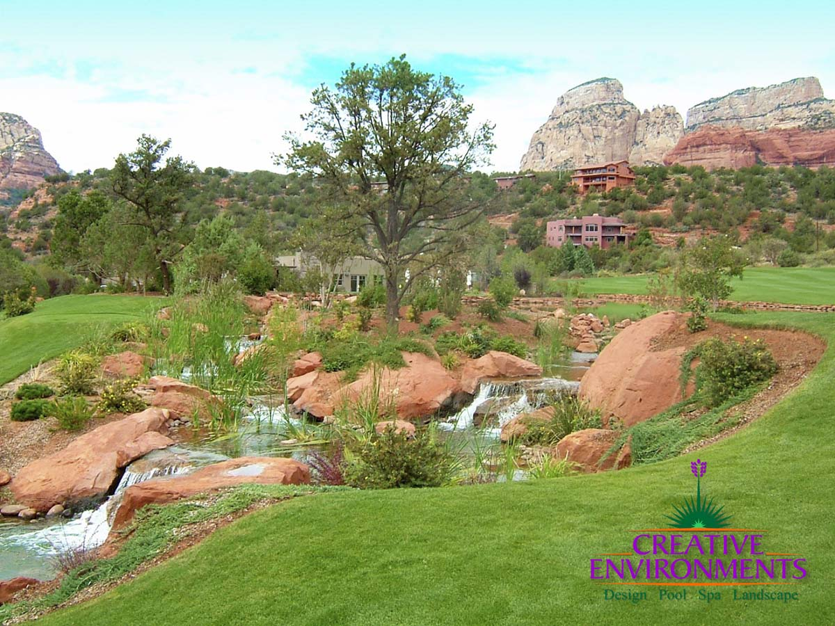 Beautiful Sedona landscape on golf course with custom natural looking waterfall around red rocks with mountains in the background