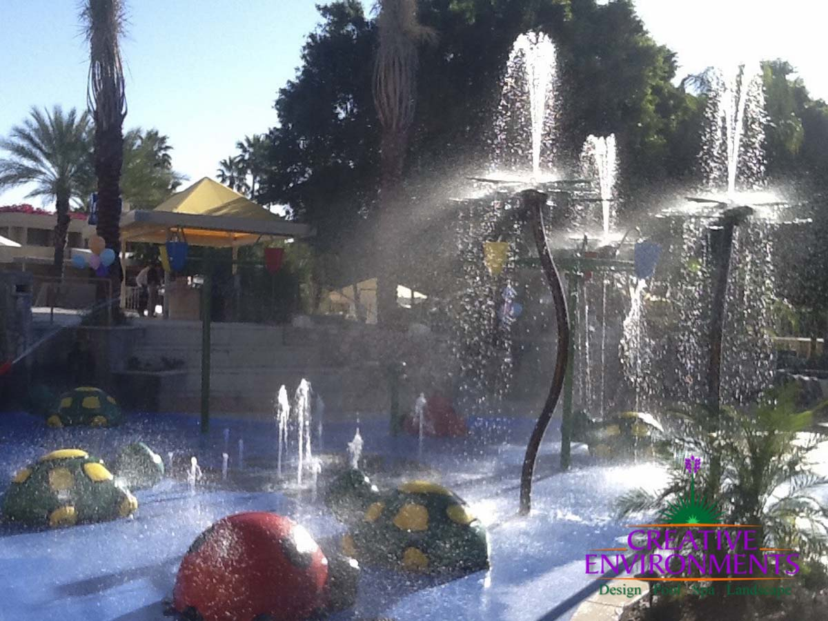 Large custom landscaped splash pad with childrens fountains and colorful water fall structures and turtles surrounded by seating area and cabanas