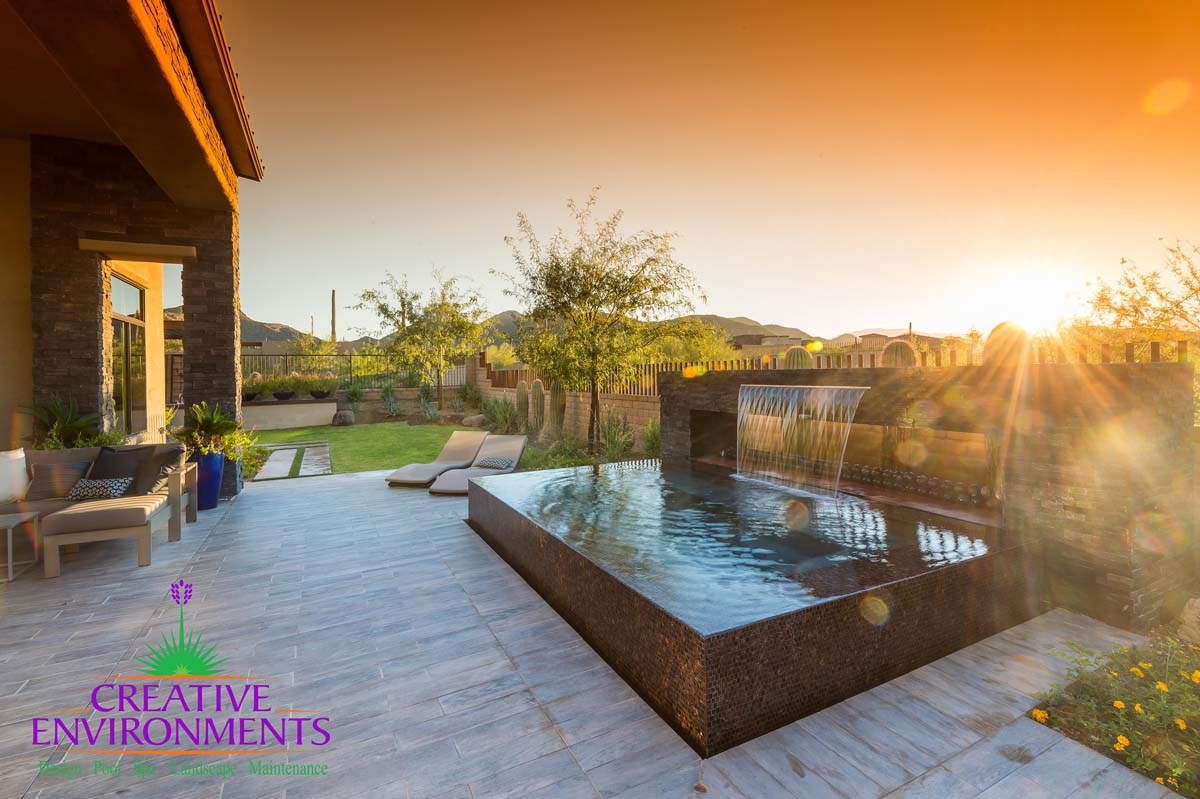 Backyard custom landscape with infinity pool and large waterfall from rock hardscape near lounge area