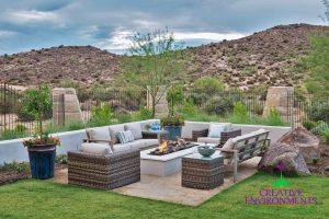 Back area of backyard with custom hardscape fire pit and seating area with desert plants and rocks