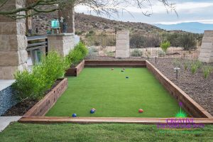 Custom artificial turf bocce ball court in backyard surrounded by desert landscaping