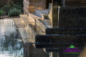 Custom hardscape floating steps to floating patio space made of wet edge pebble