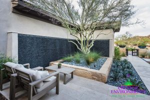 Custom front yard hardscape with large pebble wall fountain and desert landscape with seating