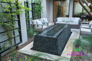Custom landscaped side yard with lounge seating, climbing plant, and central water feature with wet edge black pebble