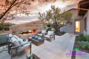 Custom side yard with large hardscape fireplace, desert trees and landscapes, and seating area