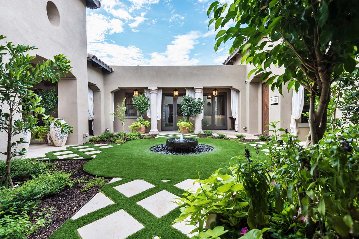Custom front yard courtyard with unique patterned artificial grass around concrete with climbing plants and custom water fountain in center