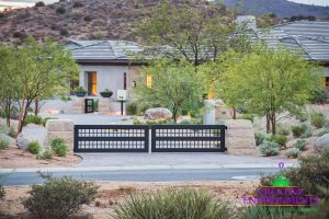 Brick paved road with custom metal fence surrounded by desert landscape leading up to home