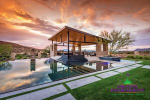 Expansive outdoor landscape with large zero edge pool, hardscape sculptures, and floating covered patio with water features and outdoor kitchen
