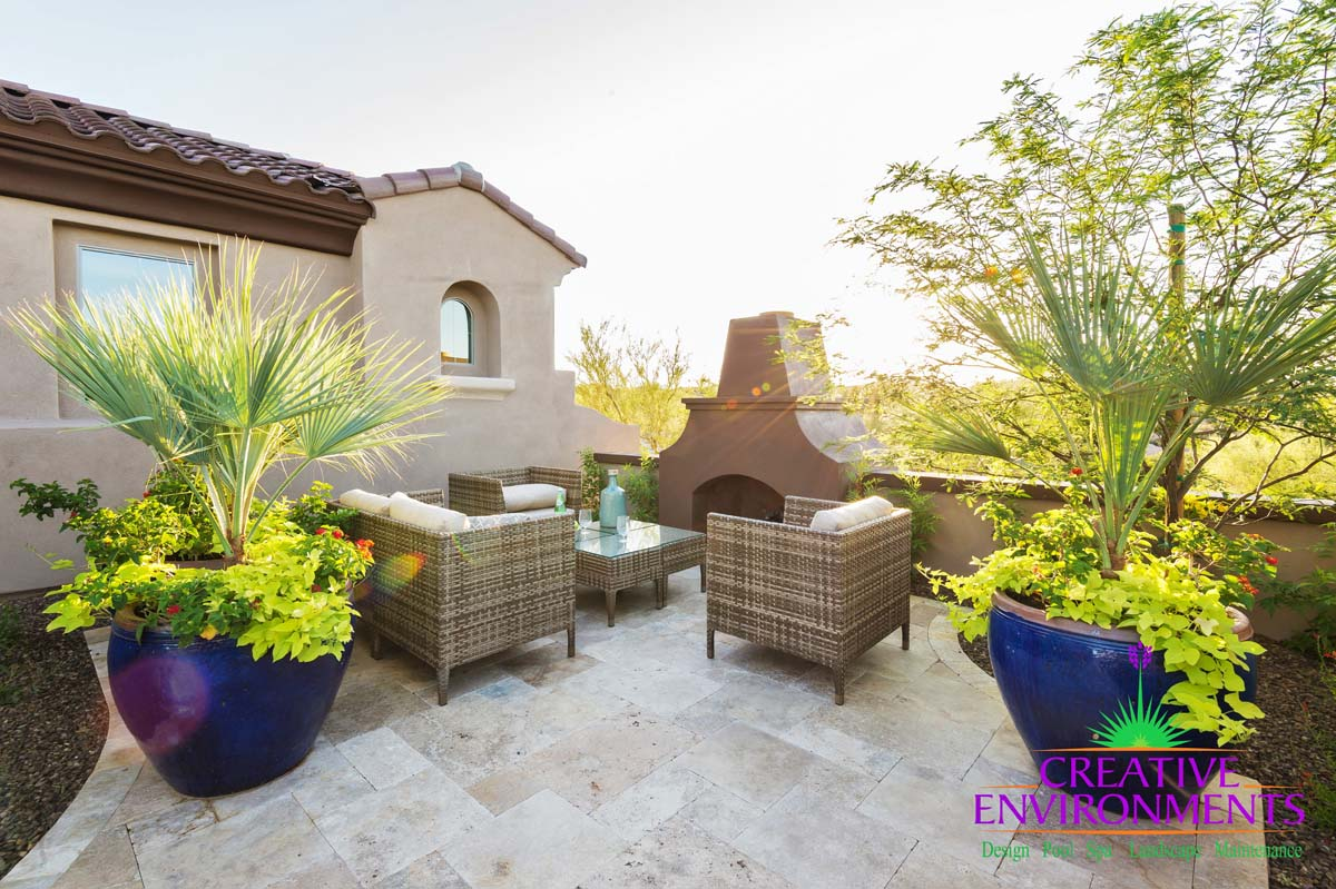Custom landscape side yard with ceramic potted plants and seating area near outdoor fireplace and desert plants