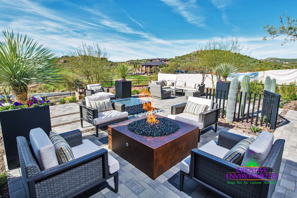 Custom fire pit area with metal fire pit and desert landscape
