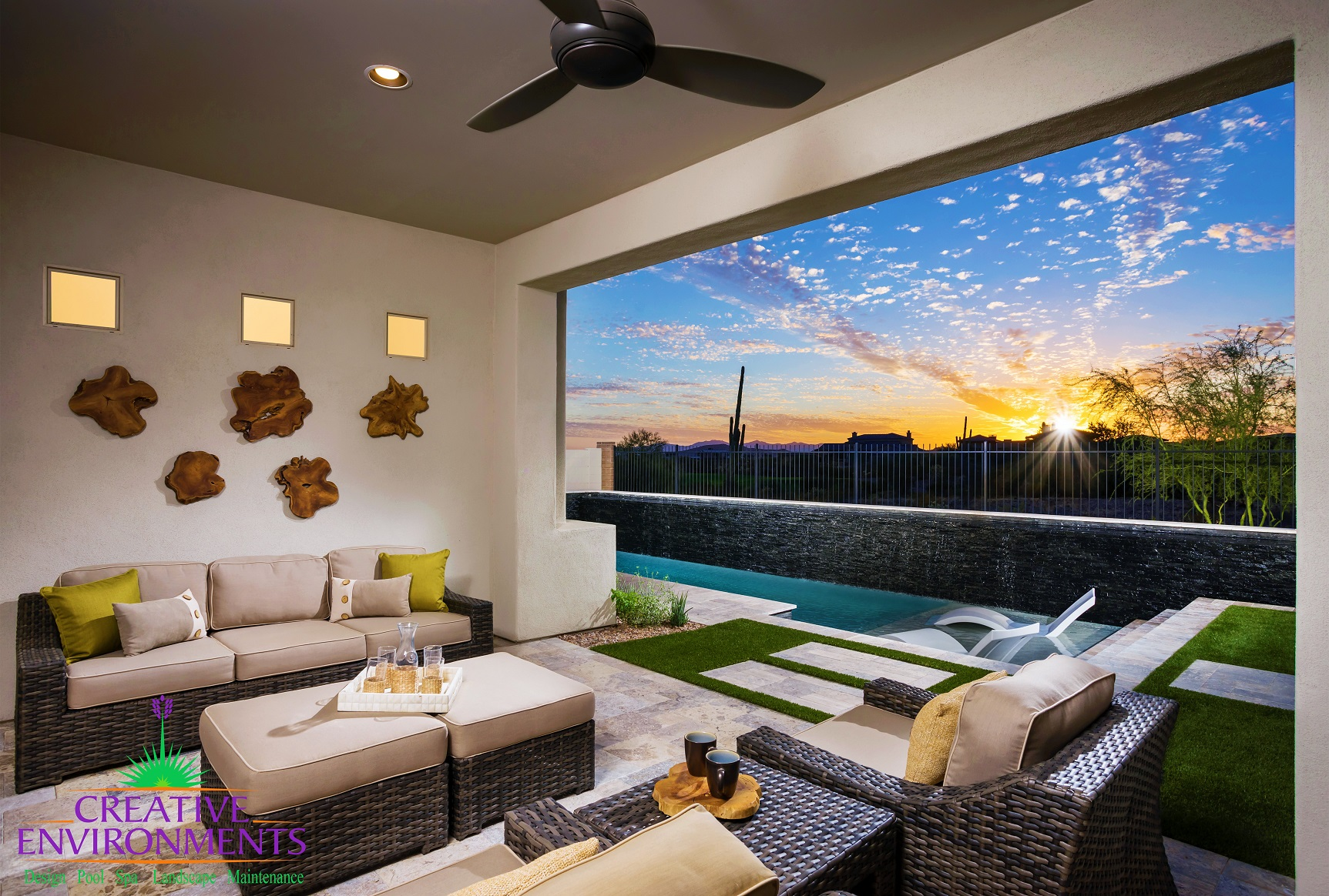 Indoor lounge area open to the backyard with a custom pool with a water feature and sunset\
