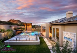 Arial view of a custom landscaped backyard with custom infinity pool, seating area, and covered patio with floating steps