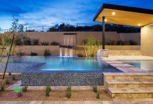 Custom backyard with waterfall leading too infinity edge pool with floating steps and covered patio with custom awning