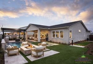 Custom outdoor landscape in Arizona backyard space with custom swimming pool and lounge seating around a fireplace