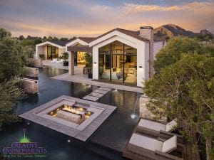 Custom outdoor landscape in Arizona showing expansive swimming pool with floating steps and firepit in center of pool