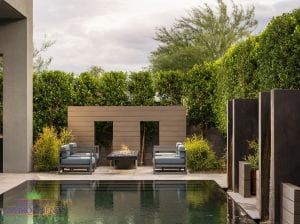 Custom outdoor landscape in Arizona in backyard near pool with a lounge area near metal art and firepit
