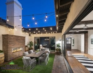 Custom outdoor landscape in Arizona side yard area with outdoor dining table and fireplace covered by string lights