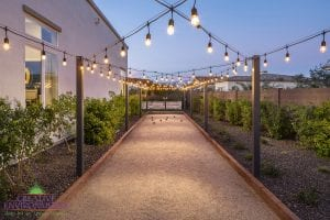 Custom outdoor landscape in Arizona backyard showing a large bocce ball court with custom string lighting above
