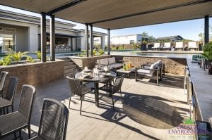 Custom outdoor landscape in Arizona covered patio with outdoor kitchen and lounge area near a zero edge swimming pool