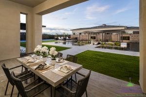 Custom outdoor landscape in Arizona backyard covered patio outdoor dining near grass area and zero edge swimming pool