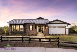 Custom outdoor landscape in Arizona front yard with grass area and Chicago brick siding surrounded by a black metal fence
