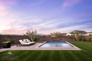 Custom outdoor landscape in Arizona backyard with swimming pool and water fountains near lounge area