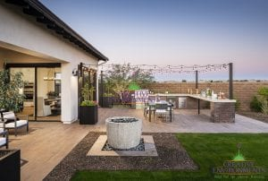 Custom outdoor landscape in Arizona backyard with outdoor kitchen and dining area with string lighting near water fountain
