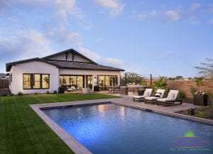Custom outdoor landscape in Arizona backyard with large swimming pool near grass and lounge area patio