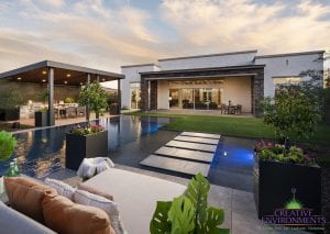 Custom outdoor landscape in Arizona backyard with grass area leading to large pool and floating steps to a patio in the center of the pool with a bed