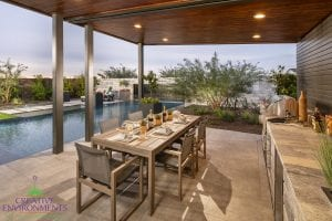 Custom outdoor landscape in Arizona backyard covered patio with outdoor kitchen and dining near lare swimming pool
