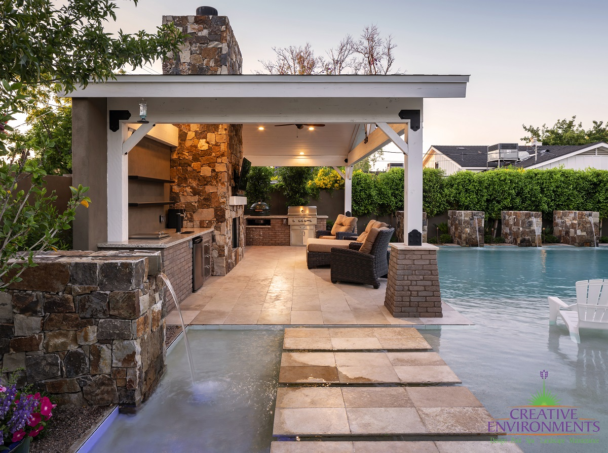 Custom backyard landscape design from floating steps on zero edge pool leading to covered patio wtih outdoor kitchen