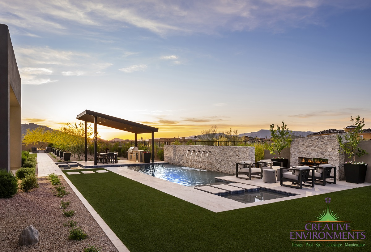 Custom backyard landscape design with a custom swimming pool surrounding by patio space, turf, and desert landscape