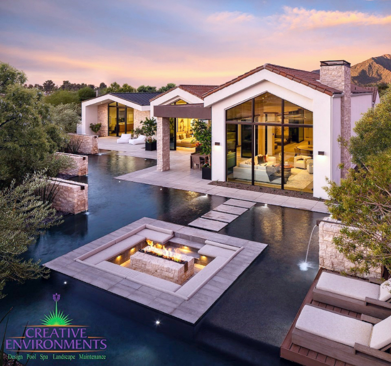 Custom backyard landscape design with large swimming pool and floating island with a firepit near a large house
