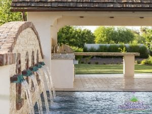 Custom outdoor landscape showing a decorative Chicago brick wall about the swimming pool with waterfall water features near a covered patio