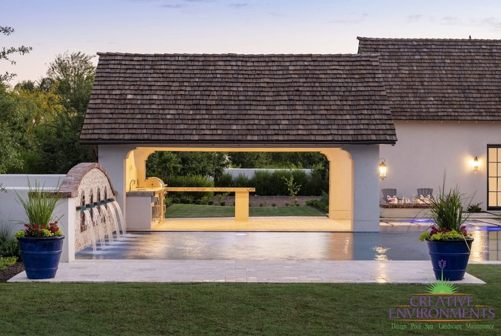 Custom outdoor landscape backyard swimming pool near a large covered patio with outdoor kitchen