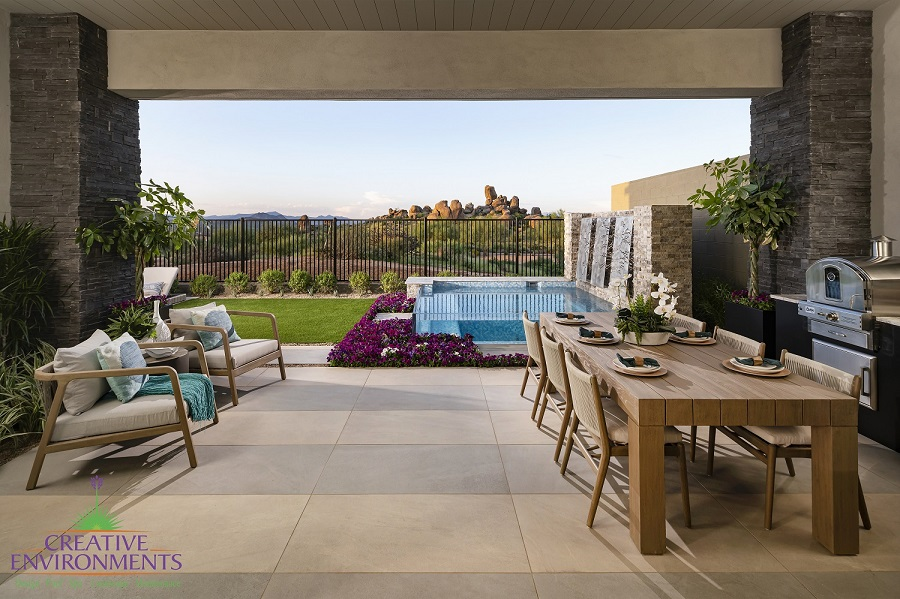 Creative Environments design and landscape at Sereno Canyon Enclave Model showing backyard patio with dining and glass swimming pool