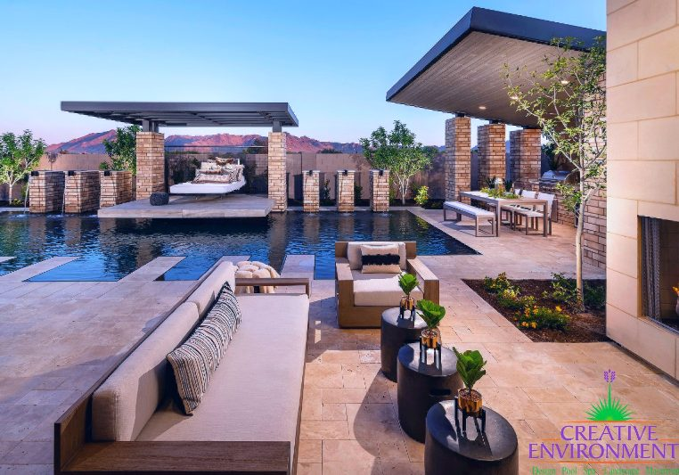 Custom backyard design landscape with patio area near fireplace and swimming pool with covered patio