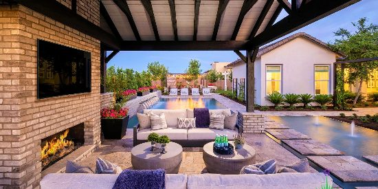 Custom backyard landscape covered patio with outdoor fireplace and seating area with a television