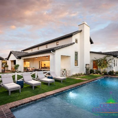 Custom backyard landscape with large swimming pool near lounge area and large white house