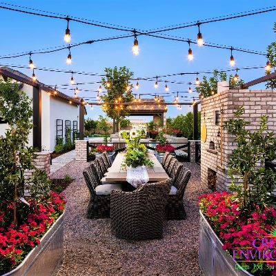 Custom backyard landscape with dining area around containter garden and pizza oven covered by rope lights