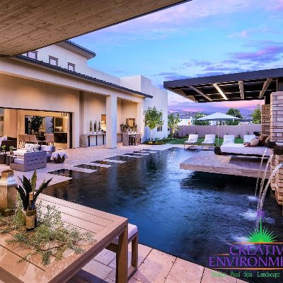 Custom backyard landscape with zero edge pool and floating bed area under covered patio