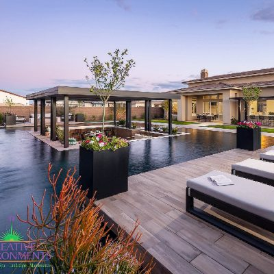 Custom backyard landscape with zero edge pool and floating covered patio area near water features