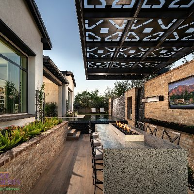 Custom backyard landscape with metal covered patio and outdoor seating near firepit