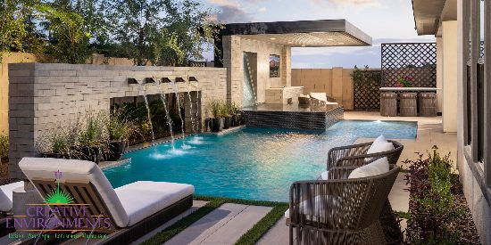 Custom backyard landscape with custom swimming pool and water feature near covered patio and hot tub space