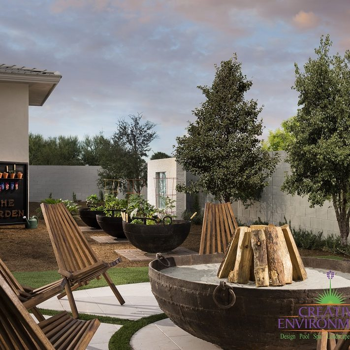 Custom backyard landscape with large metal firepit and garden area